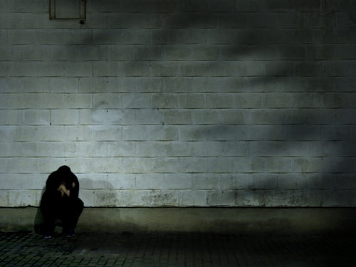 a man in black huddles against a wall as shadows reach for him
