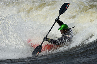 kayaker balancing in whitewater