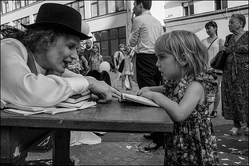 a woman talks to a little girl over an open book on a table