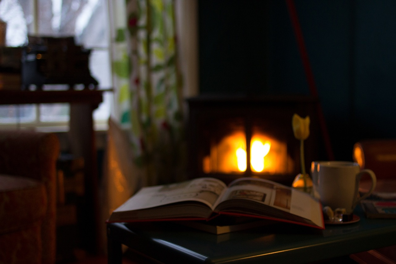 A book lies open in the foreground; a fireplace in the background near a window