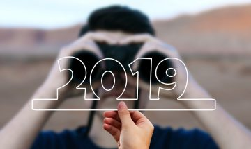 man with binoculars looks at 2019 numerals