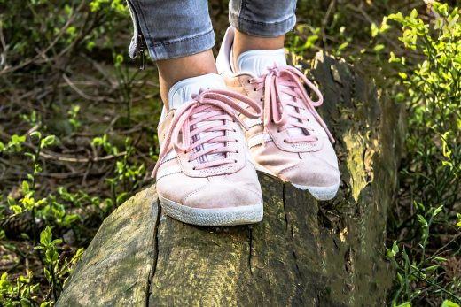 pink shoes balancing on a log