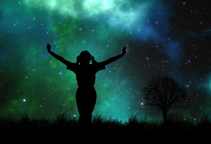 A girl's silhouette lifts her arms to the night sky